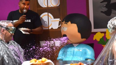 A South Park character spits purple liquid at a contestant in a trivia game in the exhibition hall at Comic-Con.
