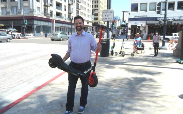 Danny Simon holds Razor electric scooter