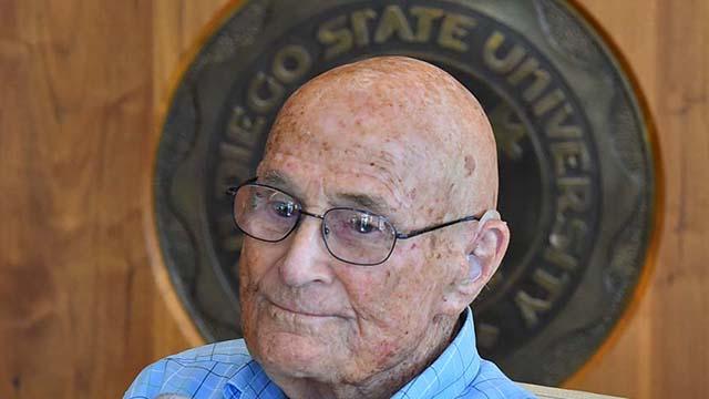 Bill Vogt, with SDSU seal behind him.