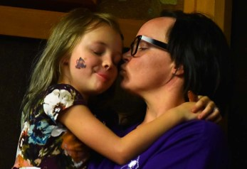 Jamie Ketelsen kisses daughter Devi while listening to her husband, Nick, of Ranchita.