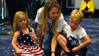 Congressional candidate Mike Levin's wife, Chrissy, keeps her children, Elizabeth and Jonathon, entertained in the back of the room before Obama arrived. Photo by Chris Stone