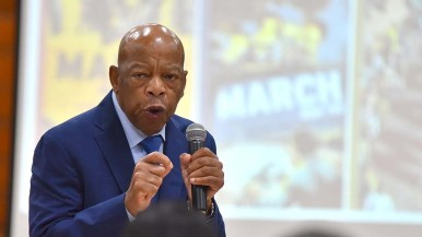"""Rep. John Lewis speaks in front of posters showing covers of his """"March"""" trilogy of comic books."""