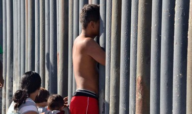 A young man along with a woman and children peer across the U.S.-Mexico border.