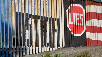 Signs are painted on the Mexican side of the border fence.