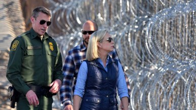 Homeland Security Secretary Kirsten Nielsen looks through the fence and wire at people in Mexico.