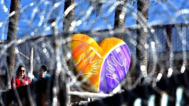 A couple on the Mexico side of the border and a heart sculpture can be seen through the newly installed concertina wire.