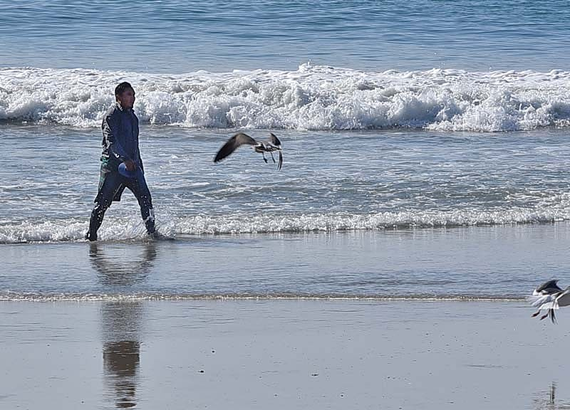 A man from Nicaragua walks on the Border Field State Park beach as Border Patrol agents get ready for a press conference with Homeland Security Secretary Kirsten Nielsen.