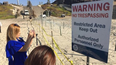 Member of the media takes picture of warning sign at Border Field State Park.