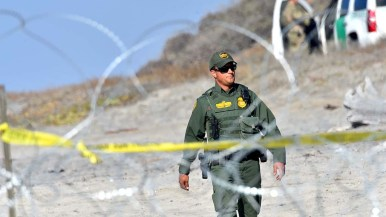 A Border Patrol agent walks toward the concertina wire set up on the beach to keep people back from the fence.