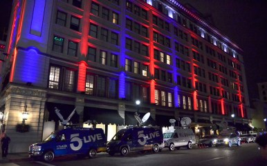 U.S. Grant Hotel's east side, flanked by TV trucks, is lit up in red and blue