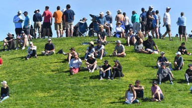 Spectators watch the 4th hole of the south course from a grassy hill.