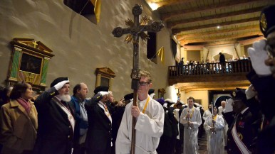 An altar server carries a cross at the head of the opening procession.