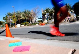 Race walker in adidas strides past spent sponges used to cool off walkers in Santee.