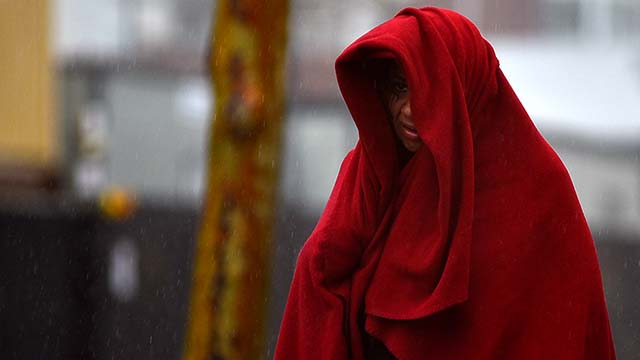A homeless woman covers herself with a red blanket in an attempt to stay dry downtown.
