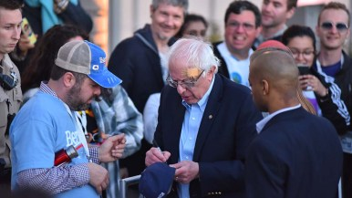 Sen. Bernie Sanders autographs a baseball hat for a fan in Waterfront Park in downtown San Diego.