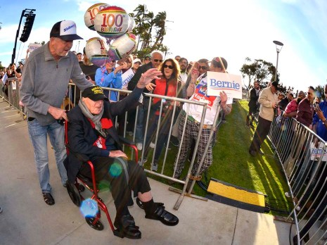 Rancho Bernardo's Sidney Walton, 100, accompanied by his son Paul, acknowledges cheers from bystanders.