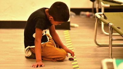 A young boy fills some of his wait time using a line on the floor as a highway for his miniature car toy.