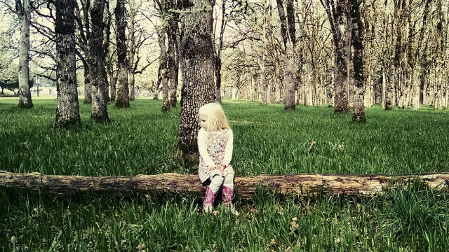 A young girl by herself in a forest