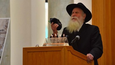 A rabbi holds a religious bag as he calls upon the women of the congregation to do good works in the name of Lori Kaye.