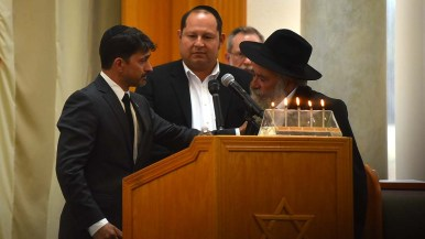 Oscar Stewart, left, who confronted the gunman Saturday has a quiet moment with Rabbi Yisroel Goldstein.
