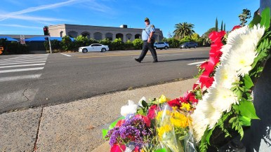 A San Diego County Sheriffs deputy crosses between the synagogue and flowers honoring the victims of the shooting.