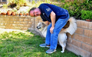Max Branscomb, with Leilani in the back yard of his Bonita home, says he lost 48 pounds amid his cancer treatment.