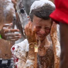 A boy is showered with water that removes the caked on mud and the soap.