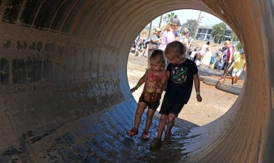 Two girls make their way through a tunnel toward a water pit on a muddy obstacle course.