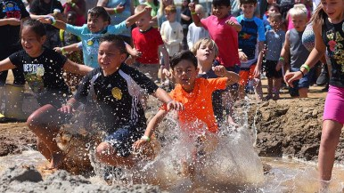 A group of children begin their run through the watery obstacle course on International Mud Day.