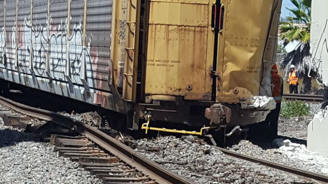 A derailed freight car beside a damaged building