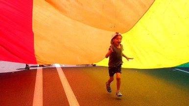 A young boy with the US Bank unit delighted in his romp under a rainbow flag carried by bank employees.