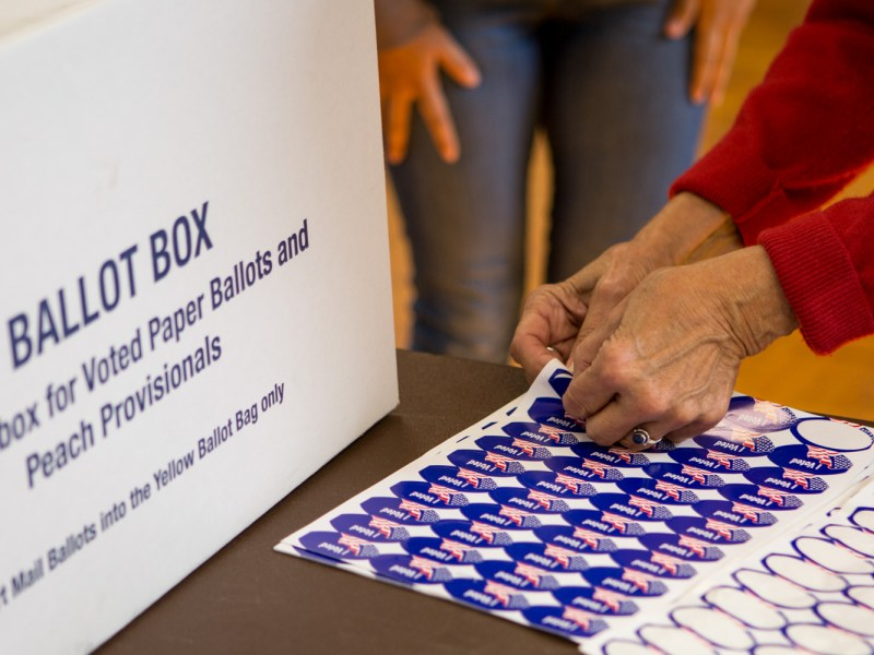 A poll worker hands out stickers at the San Ysidro Library on Election Day, Nov. 6, 2018.
