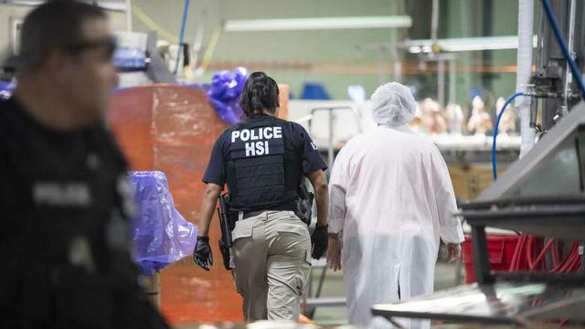ICE agent escorts chicken plant worker