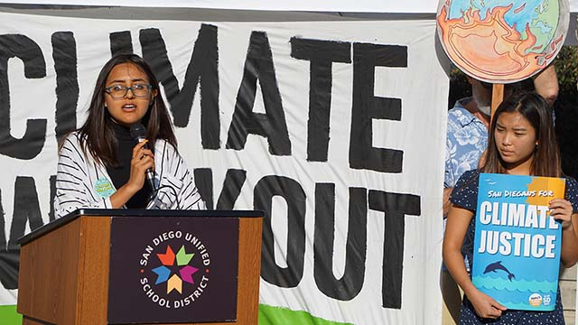 Vanessa Cascate of Mission Bay High School speaks at recent rally while Annie Annie Do of Serra High holds sign.