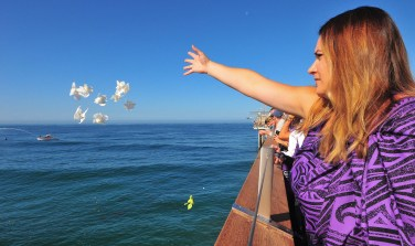 Heather Colby tosses flowers off of the Scripps Pier in honor of ocean scientist Walter Munk.