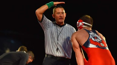 Referee signals disqualification of Fresno State's Hunter Cruz after an illegal move.