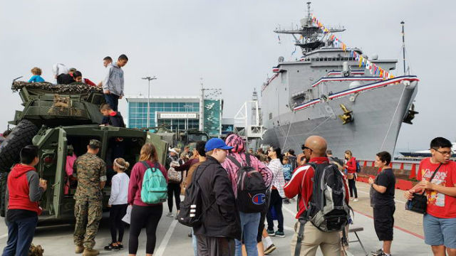 Visitors tour a ship and inspect Marine Corps equipment