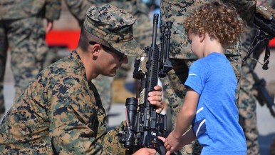 A curious young boy gets a look at military weaponry on the Broadway Pier during Fleet Week.