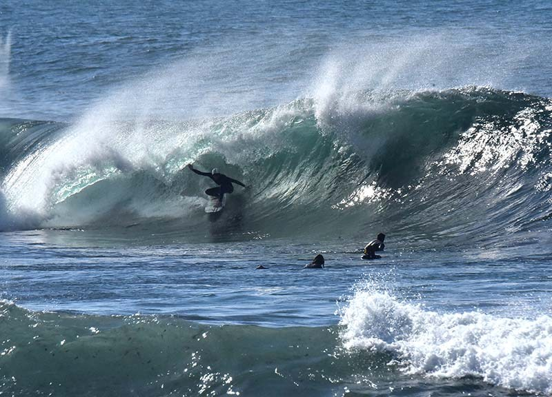 Surfers enjoy the high surf along La Jolla.
