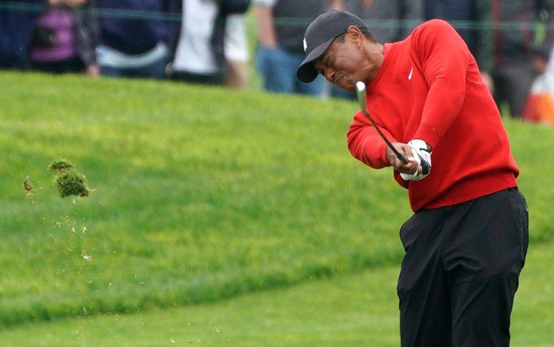 Tiger Woods creates a divot as he powers through a drive at the Farmers Insurance Open in the fourth round.