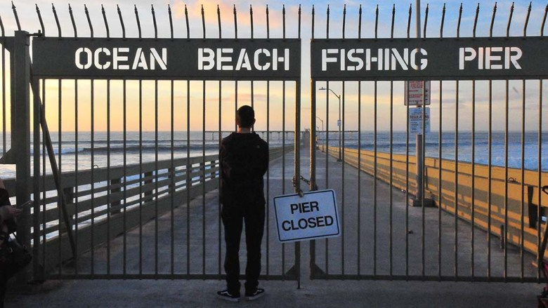On New Year's Day, a visitor stops outside gate of closed Ocean Beach Pier.