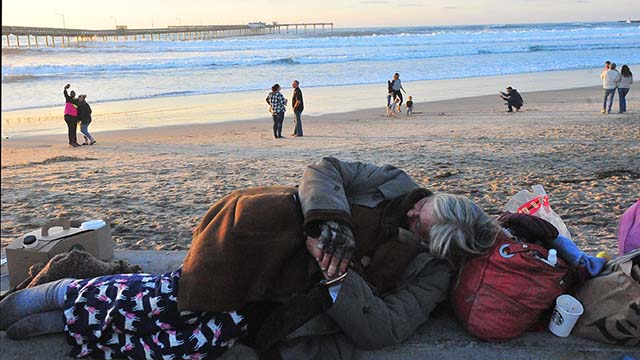 An unsheltered woman sleeps on concrete wall overlooking Ocean Beach Pier and New Year's Day visitors taking selfies at sunset.