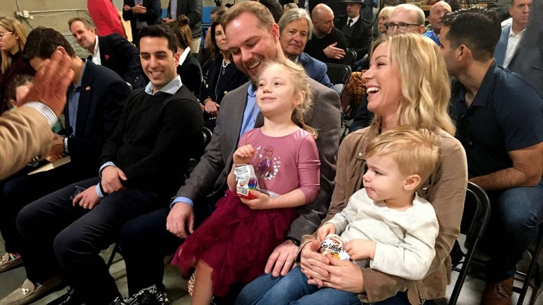 Zachary Lewis held daughter Ariana, while wife Jamie sat with son Gage at Fuse Integration event for Mike Bloomberg