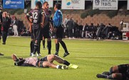 Two injured players remain on the pitch as a referee sorts out the action.