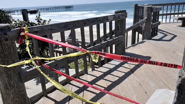 Police caution tape prevent people from taking stairs down to Pacific Beach.