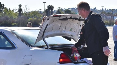 San Diego Mayor Kevin Faulconer lens a hand by putting food in the trunk at a food giveaway for 1,000 cars at SDCCU Stadium.