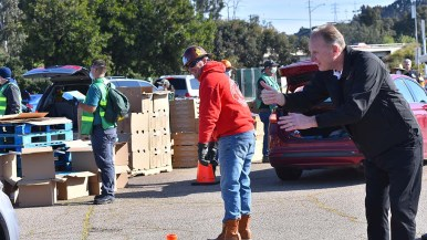 San Diego Mayor Kevin Faulconer gives a thumbs up to San Diegans participating in a food giveaway at SDCCD Stadium.