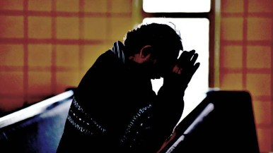 A man prays in a darkened St. Rose of Lima in Chula Vista on Palm Sunday.
