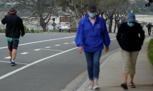 People in face masks walk in Del Mar