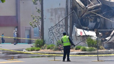 Workers install temporary fences are two banks that were burned during a night of fires and looting in downtown La Mesa.